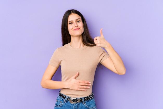 Jeune femme de race blanche sur le mur violet touche le ventre, sourit doucement