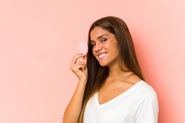 Jeune femme de race blanche nettoyant son visage avec un disque facial isolé