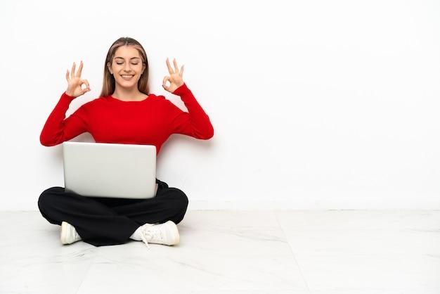 Jeune femme de race blanche avec un ordinateur portable assis sur le sol en pose zen