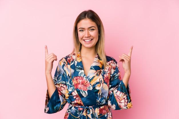 Jeune femme de race blanche portant un pyjama indique avec les deux doigts avant montrant un espace vide.