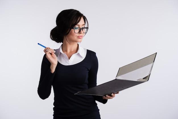 Jeune femme de race blanche portant une robe bleu foncé, chemise blanche, tenant un classeur à anneaux et un stylo.