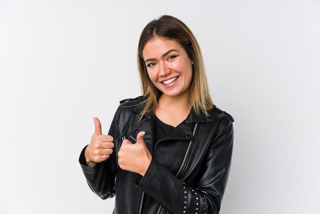 Jeune femme de race blanche portant une veste en cuir noire soulevant les deux pouces vers le haut, souriant et confiant.