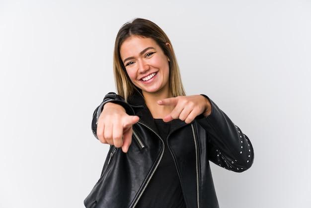 Jeune femme de race blanche portant une veste en cuir noire sourires joyeux pointant vers l'avant.