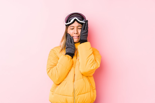 Jeune femme de race blanche portant un vêtement de ski dans un mur rose pleurnicher et pleurer inconsolablement.