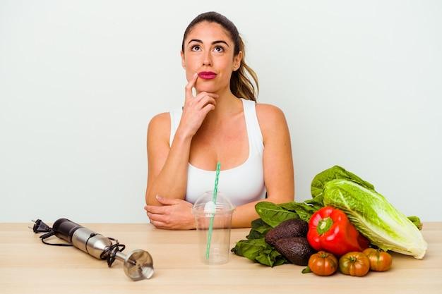Jeune femme de race blanche prépare un smoothie sain avec des légumes à la recherche de côté avec une expression douteuse et sceptique.