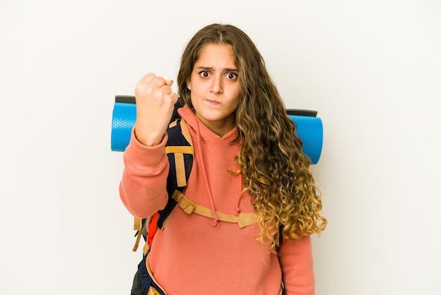 Jeune femme de race blanche prête pour un voyage isolé montrant le poing à l'avant, expression faciale agressive