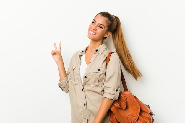 Jeune femme de race blanche prête pour un voyage joyeux et insouciant montrant un symbole de paix avec les doigts.