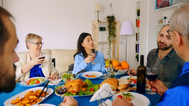 Jeune femme de race blanche et sa mère buvant du vin au dîner de famille.