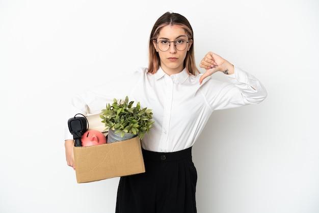 Jeune femme de race blanche se déplaçant dans une nouvelle maison parmi les boîtes isolées sur fond blanc montrant le pouce vers le bas avec une expression négative