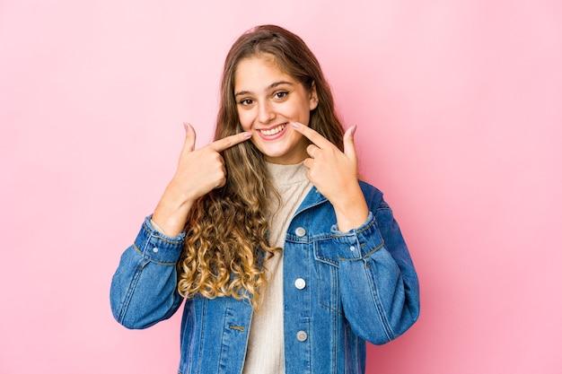 Jeune femme de race blanche sourit, pointant du doigt la bouche.