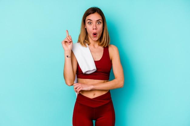 Jeune femme de race blanche sport isolée sur un mur bleu ayant une excellente idée, concept de créativité.