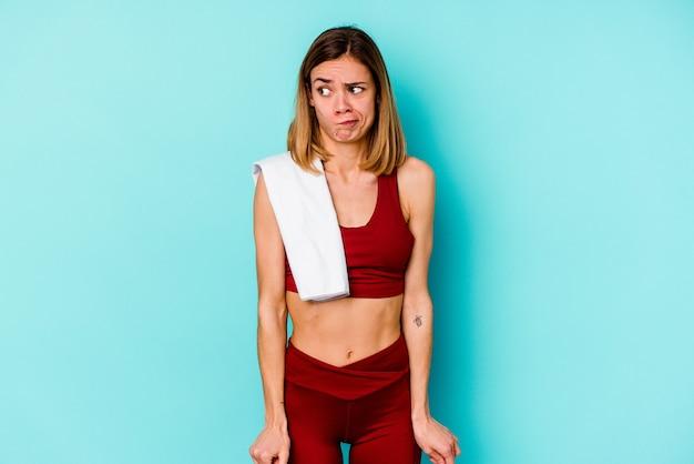 Jeune femme de race blanche sport isolée sur un mur bleu confus, se sent douteux et incertain