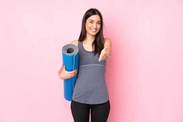 Jeune femme de race blanche avec tapis isolé sur le mur rose poignée de main après une bonne affaire