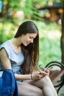 Jeune femme de race blanche avec un téléphone portable, assis dans un parc sur un banc en bois, lisant un sms.