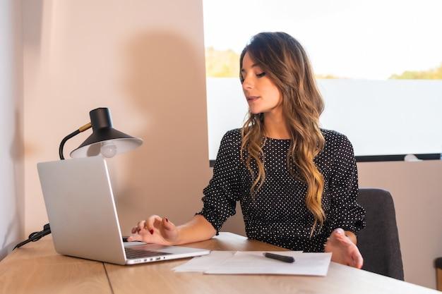 Jeune femme de race blanche télétravaillant avec un ordinateur, lisant des e-mails le matin