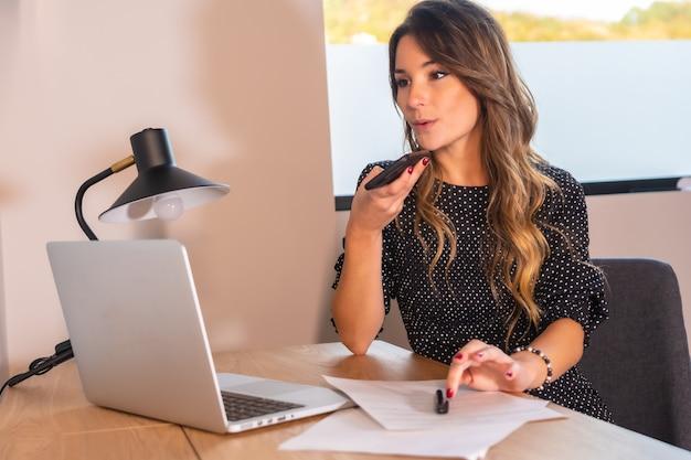 Jeune femme de race blanche télétravaillant avec un ordinateur à la maison, envoyant un message audio