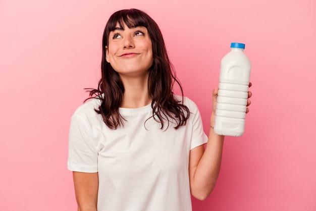 Jeune femme de race blanche tenant une bouteille de lait isolée sur un mur rose rêvant d'atteindre les objectifs et les fins
