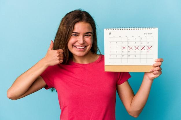 Jeune femme de race blanche tenant un calendrier isolé sur fond bleu