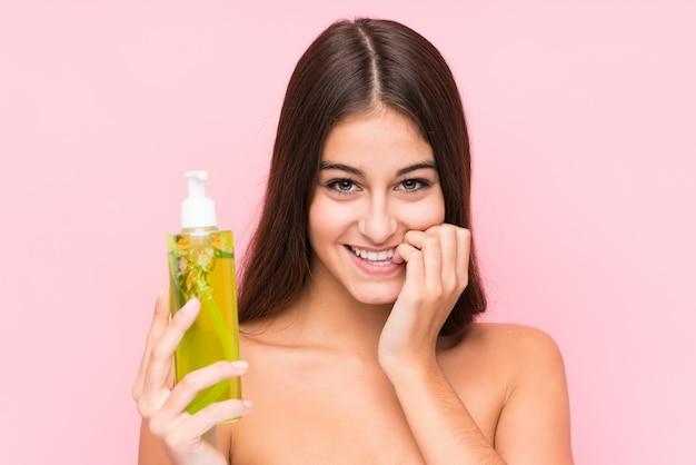 Jeune femme de race blanche tenant une crème hydratante à l'aloe vera isolé se ronger les ongles, nerveux et très anxieux.