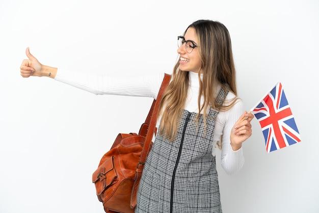 Jeune femme de race blanche tenant un drapeau du royaume-uni isolé sur fond blanc donnant un geste de pouce en l'air
