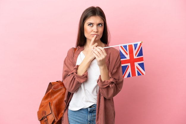 Jeune femme de race blanche tenant un drapeau du royaume-uni isolé sur fond rose ayant des doutes tout en levant