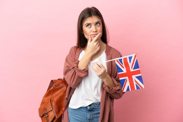 Jeune femme de race blanche tenant un drapeau du royaume-uni isolé sur fond rose ayant des doutes
