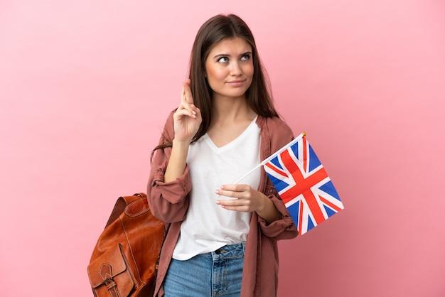 Jeune femme de race blanche tenant un drapeau du royaume-uni isolé sur fond rose avec les doigts croisés et souhaitant le meilleur