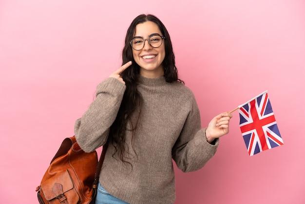 Jeune femme de race blanche tenant un drapeau du royaume-uni isolé sur fond rose donnant un geste de pouce en l'air