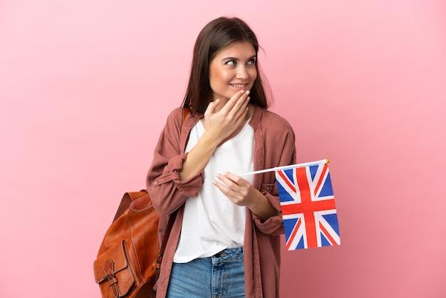 Jeune femme de race blanche tenant un drapeau du royaume-uni isolé sur fond rose en levant tout en souriant