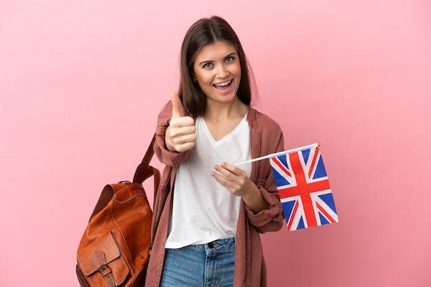 Jeune femme de race blanche tenant un drapeau du royaume-uni isolé sur fond rose avec les pouces vers le haut parce que quelque chose de bien s'est produit