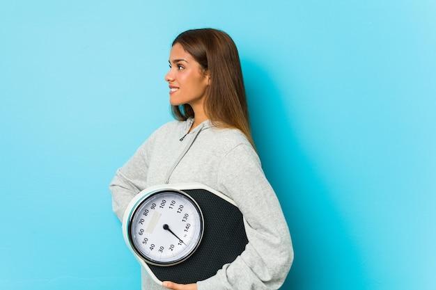 Jeune femme de race blanche tenant une échelle isolée sur un mur bleu