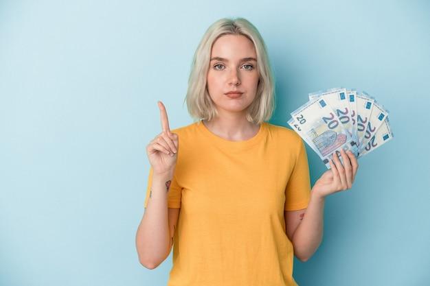 Jeune femme de race blanche tenant des factures isolées sur fond bleu montrant le numéro un avec le doigt.
