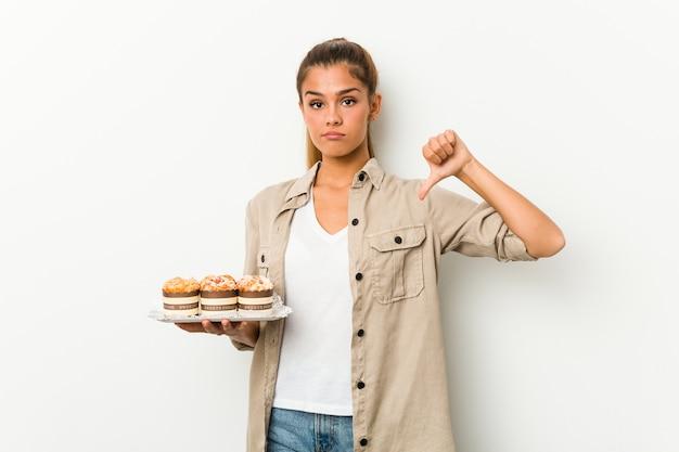 Jeune femme de race blanche tenant des gâteaux sucrés montrant un geste d'aversion, les pouces vers le bas. concept de désaccord.