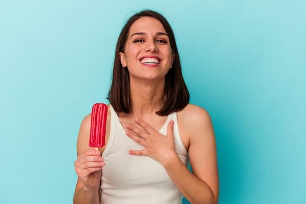Jeune femme de race blanche tenant une glace isolée sur fond bleu éclate de rire en gardant la main sur la poitrine.