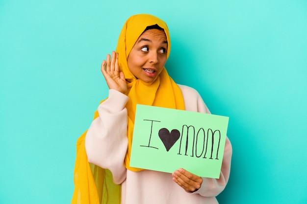 Jeune femme de race blanche tenant un j'aime maman isolée sur un mur rose en essayant d'écouter un commérage.
