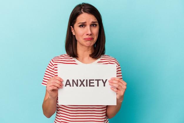Jeune femme de race blanche tenant une pancarte d'anxiété isolée sur fond bleu