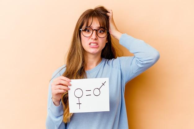 Jeune femme de race blanche tenant une pancarte d'égalité des sexes isolée étant choquée, elle s'est souvenue d'une réunion importante