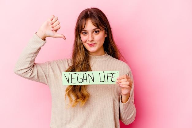 Jeune femme de race blanche tenant une pancarte de vie végétalienne se sent fière et confiante, exemple à suivre.