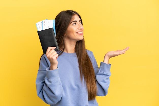 Jeune femme de race blanche tenant un passeport isolé sur fond jaune tendant les mains sur le côté pour inviter à venir