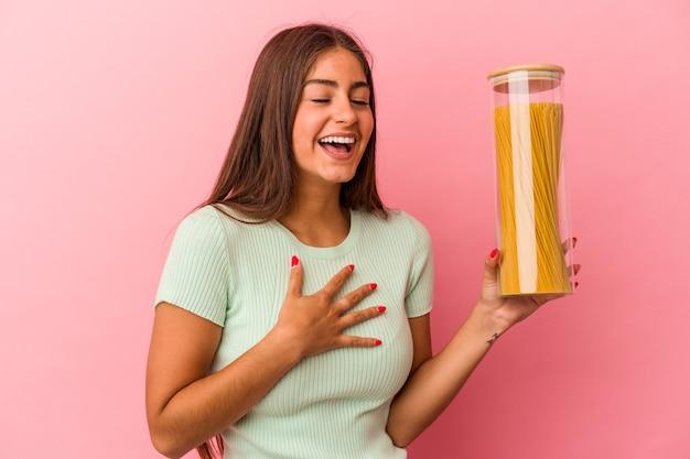 Jeune femme de race blanche tenant un pot de pâtes isolé sur fond rose éclate de rire en gardant la main sur la poitrine.