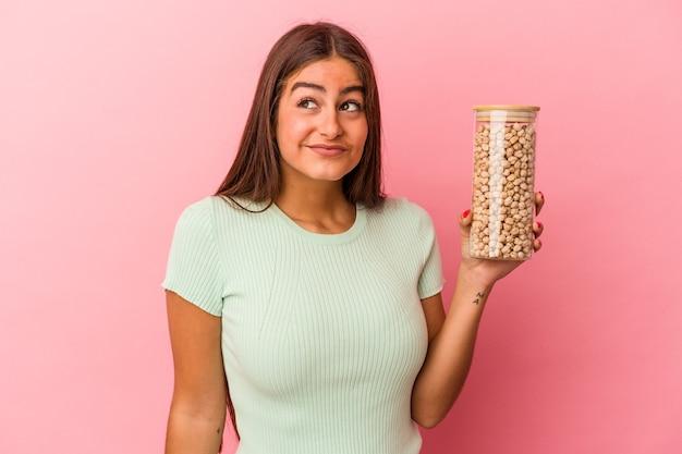 Jeune femme de race blanche tenant un pot de pois chiches isolé sur fond rose rêvant d'atteindre des objectifs et des objectifs
