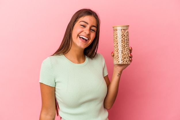 Jeune femme de race blanche tenant un pot de pois chiches isolé sur fond rose en riant et en s'amusant.