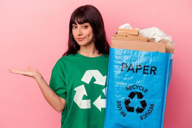 Jeune femme de race blanche tenant un sac en carton recyclé isolé sur fond rose montrant un espace de copie sur une paume et tenant une autre main sur la taille.