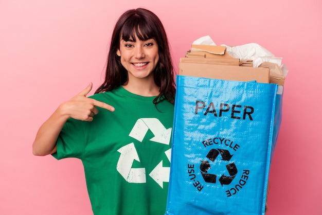 Jeune femme de race blanche tenant un sac en carton recyclé isolé sur mur rose personne pointant à la main vers un espace de copie de chemise, fier et confiant