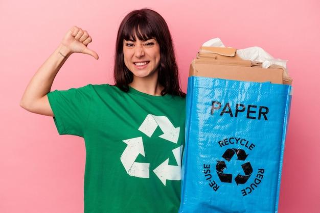 Jeune femme de race blanche tenant un sac en carton recyclé isolé sur un mur rose se sent fier et confiant, exemple à suivre.