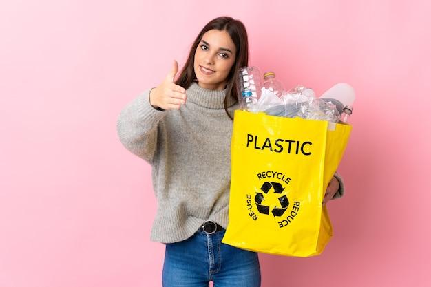 Jeune femme de race blanche tenant un sac plein de bouteilles en plastique à recycler isolé sur mur rose se serrant la main pour conclure une bonne affaire