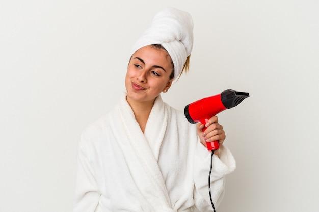 Jeune femme de race blanche tenant un sèche-cheveux isolé sur blanc rêvant d'atteindre les objectifs et buts