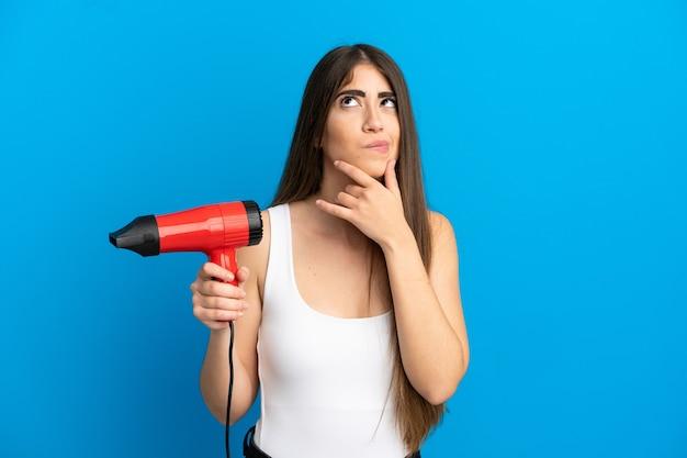 Jeune femme de race blanche tenant un sèche-cheveux isolé sur fond bleu et levant