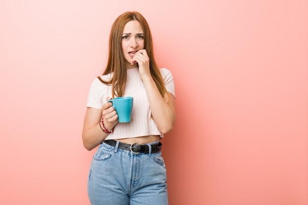 Jeune femme de race blanche tenant une tasse se mordant les ongles, nerveux et très inquiet.