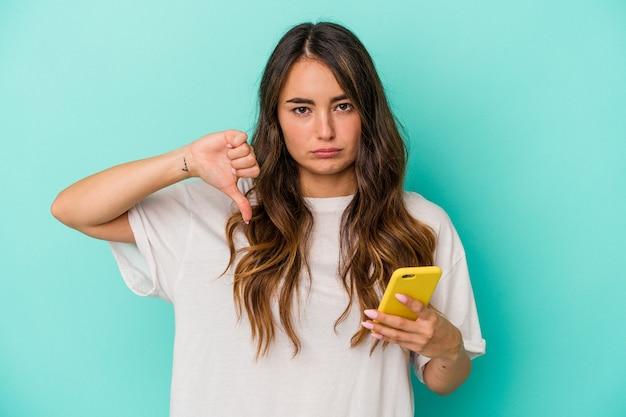 Jeune femme de race blanche tenant un téléphone portable isolé sur fond bleu montrant un geste d'aversion, les pouces vers le bas. notion de désaccord.